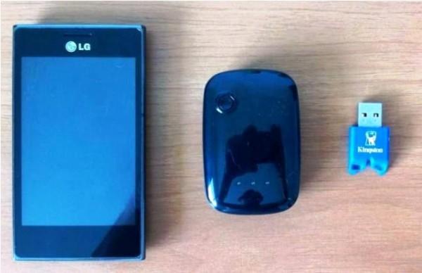 Comparativo de tamanho entre o rastreador (centro) e um pendrive (direita) e um celular (esquerda)