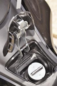 Compartimento do tanque de combustível no túnel central. Embutido e aberto mediante botão de destravamento.